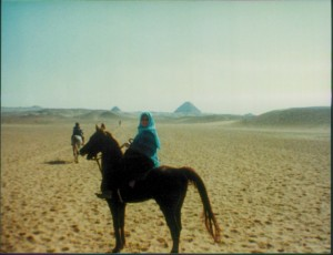Scanned photo of Mary Mimi Hassouna riding in Egypt by the pyramids.